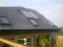 2 x Navitron flat solar water heating panels integrated into the slate roof to look similar to skylights, Brighouse, West Yorkshire